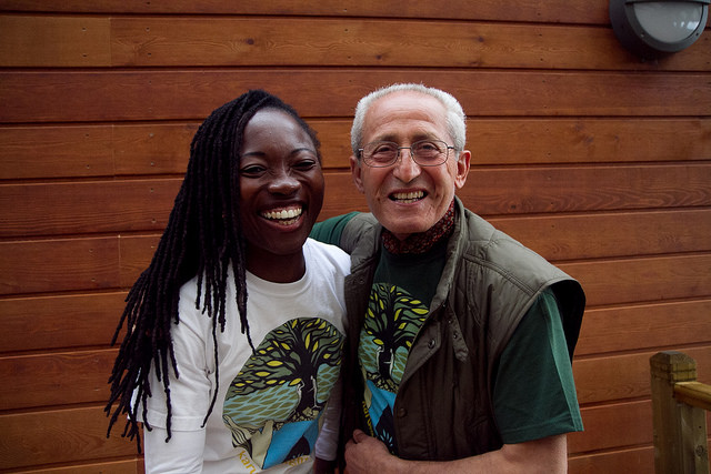 Two members at a convergence smile for the camera. They are wearing t-shirts designed by Karuna Insight Design.