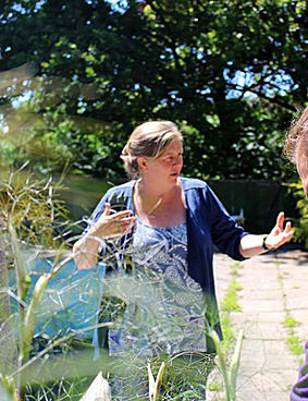 Sarah Pugh talking to permaculture students in a sunlit garden